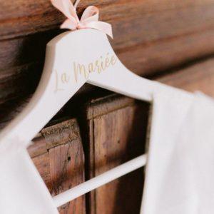 cintre de mariage blanc avec prenoms ecrits en dore et decoration avec un noeud en satin