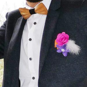 Boutonnière de marie origami aux couleurs pep's fleurs en papier fushia orange et violet avec une decoration en plume