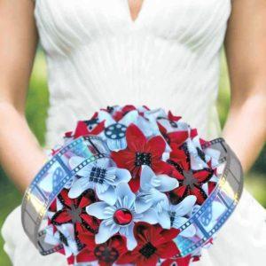 bouquet de mariee origami theme cinema -création personnalisée de fleurs en papier en forme d etoile faites a la min de couleur rouge et blanc avec decoration de bobines de cinema et de pellicules photo en noir par idealisa.