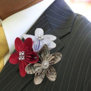 boutonniere de marie origami blanc, rouge et page de livre boutonniere homme en fleurs en etoile origami avec decoration en perle et strass idealisa