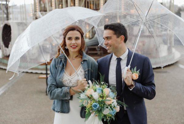 couple de maries sous la pluie avec parapluies transparents