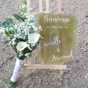 Panneau de bienvenue avec ecriture blanche en calligraphie sur un planneau en plexiglas sur fond doré
