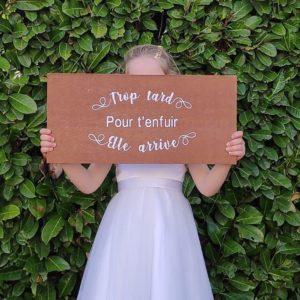 pancarte trop tard pour t'enfuir elle arrive avec ecriture blanche sur bois vernis