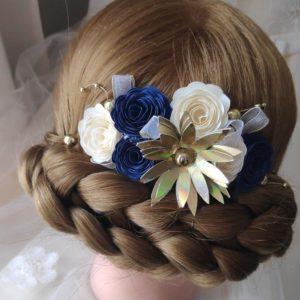 accessoire de cheveux origami bleu et dore realise avec du papier et monte sur un peigne a chignon
