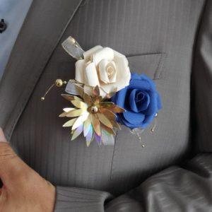 boutonniere de marie origami bleue, creme et doree avec roses petites roses eternelles reaalises avec du papier origami