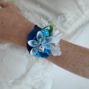 bracelet de mariage origami alice au pays des merveilles avec des fleurs bleues et blanches et du feuillage artificiel