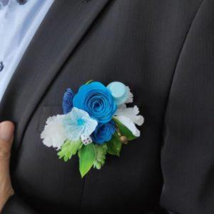boutonniere de marie origami alice au pays des merveilles avec des felurs bleu roi bleu turquoise et blanche et decoration de d chapeau et cle